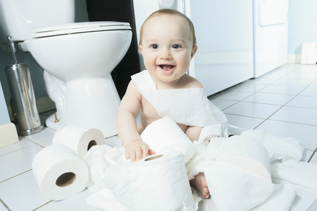 bad behavior: A Toddler ripping up toilet paper in bathroom Stock Photo