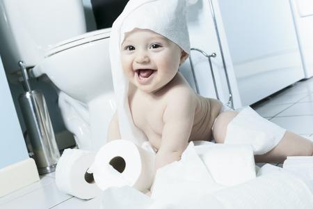 papel de baño: Niño rasgadura de papel higiénico en el baño