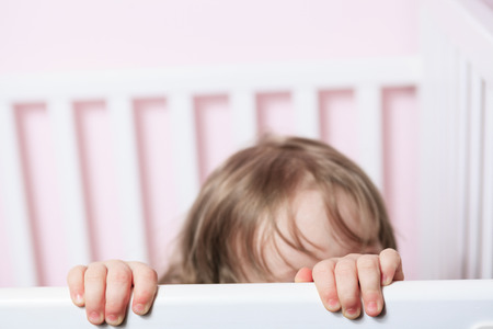babyface: A baby in his crib with pink background