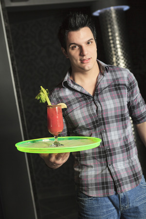 dring: A waiter at a bar bring a dring to a client. Stock Photo