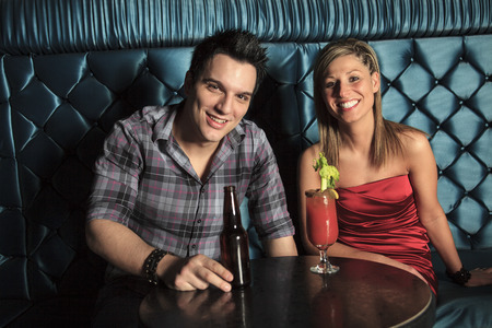 drinking alcohol: A couple drinking alcohol at a bar.
