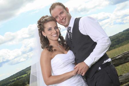 hay field: A bride and groom near hay field