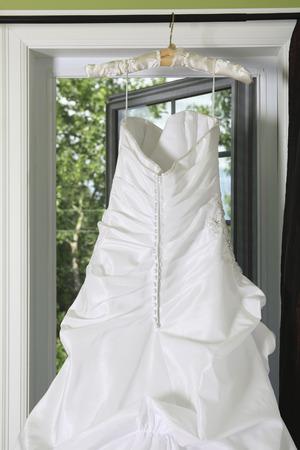 generic location: Hanging Wedding Dress in front of window