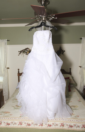 A wedding dress hanging on luster at hotel room