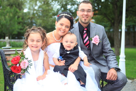 wed: A newly wed couple and children with wedding gown, dark suit and rose bridal bouquet: sit on meadow proud and happy
