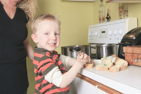 licking finger: Family cooking in their kitchen - mother making some bread. Stock Photo