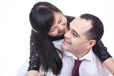 Portrait of smiling couple embracing on white background