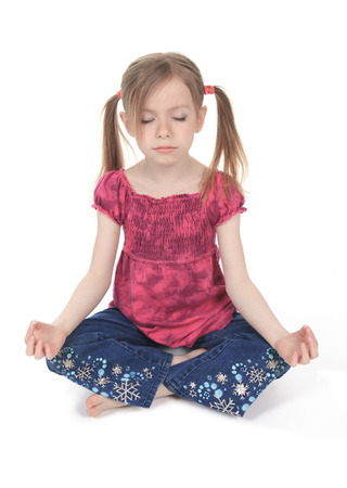 A child wearing a pink clothe doing yoga on studio.
