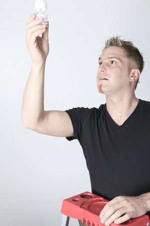 household fixture: A man changing bulb in studio gray background.