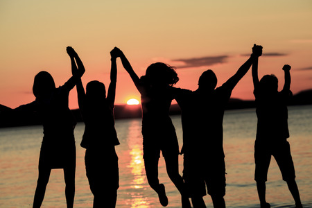 five People silhouettes jumping on summer sunset meadow Stock Photo