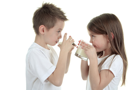 7 9 years: Little boy and girl drinking milk on white background. Studio shot