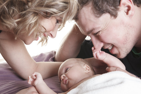 A beautiful couple with Baby on bed. Stock Photo