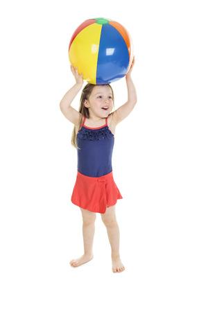 어린 소녀: A little girl holding a beach ball
