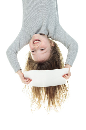 upside down: Young girl upside down isolated in white Stock Photo