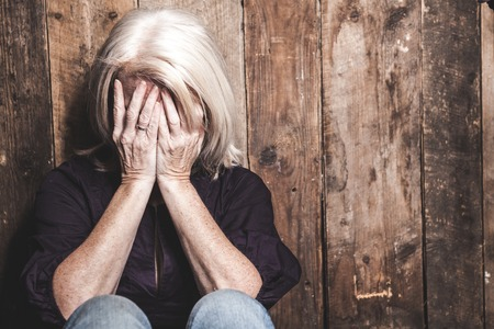 A sad senior woman with a wood background