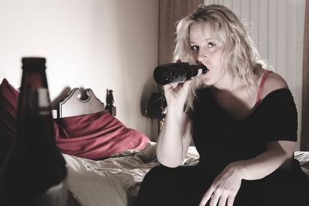 Een alcoholische vrouw drinken bier in zijn slaapkamer.