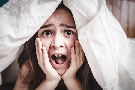 paralyze: This white Caucasian young teenage girl hides under his blankets and covers Stock Photo