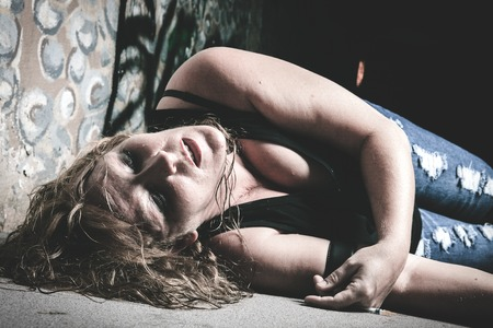 vain: A woman lay into the ground having drug in vain in a dark place.