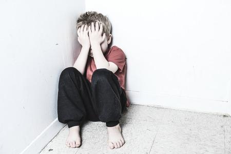 maltrato infantil: Un niño solitario Olvidadas se inclina en la pared Foto de archivo