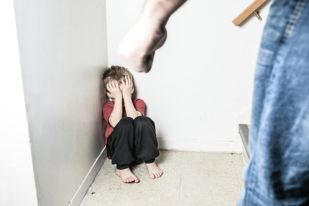 父の拳で壁の上だけで前かがみに座って男の子