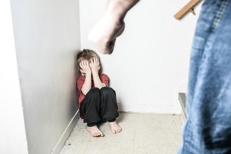 maltrato infantil: Un niño sentado solo apoyado en la pared con el puño padre
