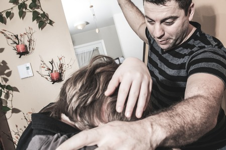 cowering: A violent father hit the teenager of the family Stock Photo