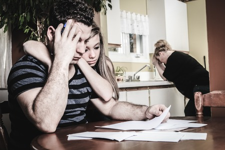 A men with financial stress at home table with teen trying to help Stock Photo