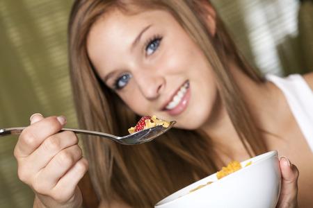 comiendo cereal: Un Adolescente comer un desayuno en la mesa de la cocina