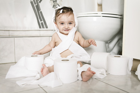 A Toddler ripping up toilet paper in bathroom Stock Photo