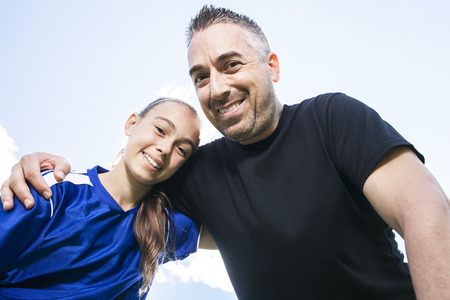 teenage guy: A teenager girl with his father play soccer in a beautiful day Stock Photo