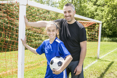 teenage girl: A teenager girl with his father play soccer in a beautiful day Stock Photo