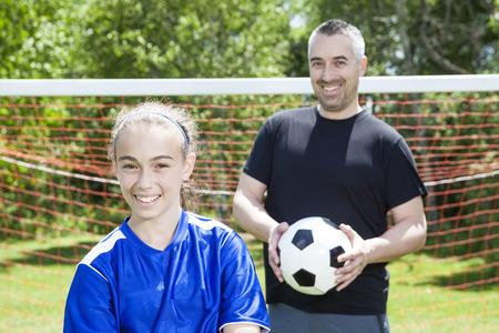 jeune fille adolescente: Une adolescente avec son père jouer au soccer dans une belle journée