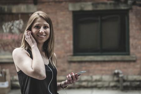 earphone: A young beautiful woman in town listening music earphone