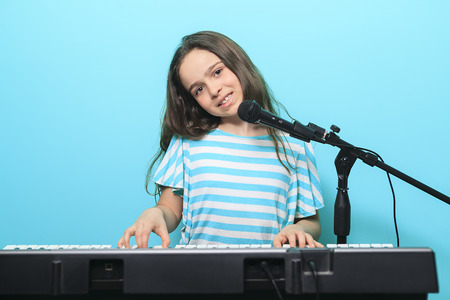 teach: A Young girl play digital piano in the living room