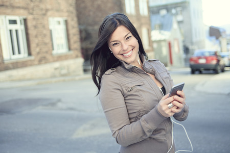 earphone: A young beauty posing over an urban city with earphone and phone
