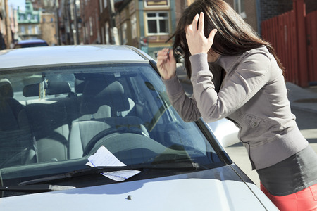 An unhappy woman with ticket on car