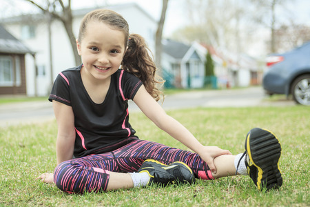 caucasian white: A girl stretching outside in spring season. Stock Photo
