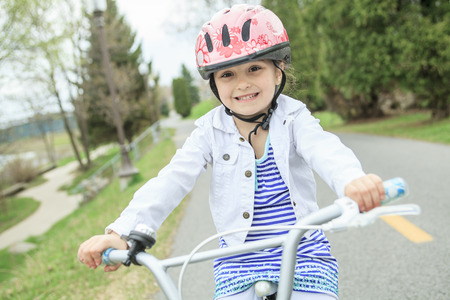 one child: A Little girl riding a bike on spring season.