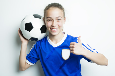 kids football: A girl in sport wear with football isolated on white background Stock Photo