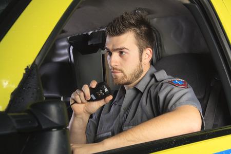 マイクで話している彼の救急車のホイールで救急救命士。
