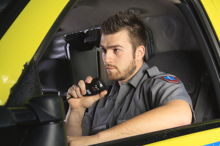 A paramedic at the wheel of his ambulance talking on microphone. Foto de archivo