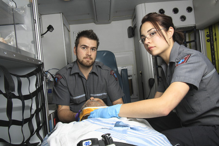 A team of professional paramedics giving unconscious men first aid