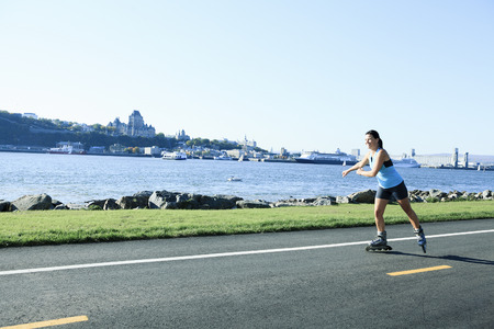 rollerblade: A wide angle of a woman with is rollerblade in summer time