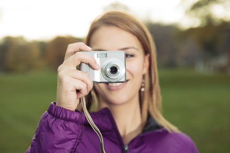 photocamera: A Portrait of young charming woman holding photocamera and taking photo at autumn Stock Photo