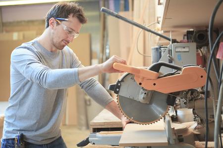 Carpenter pracuje ciężko z piłą w sklepie. Zdjęcie Seryjne