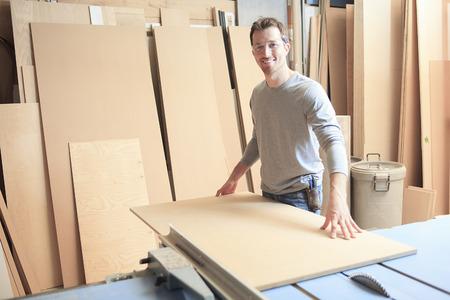 carpenter: A carpenter working hard at the workshop. Cutting wood.