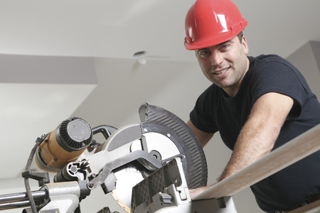 casco rojo: Un trabajador de la construcción con el casco rojo de trabajo con una sierra.