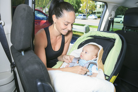 working mother: A sport woman with a baby on his car. Stock Photo