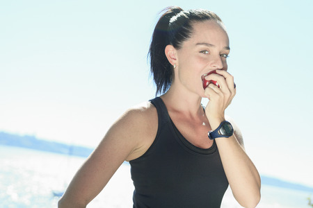 cardiovascular exercising: A happy sport woman with an apple on his hand on the sea border.