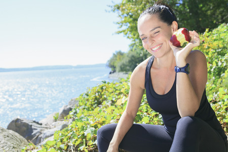 pomme: A happy sport woman with an apple on his hand on the sea border.